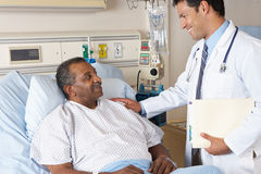 Doctor Visiting Senior Male Patient On Ward Royalty Free Stock Image