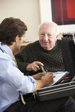 Doctor visiting senior man at home Stock Photography