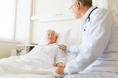 Doctor visiting senior woman at hospital ward Stock Images