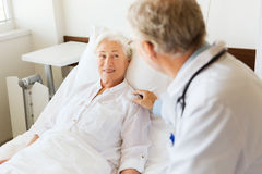 Doctor visiting senior woman at hospital ward Stock Image