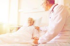 Doctor visiting senior woman at hospital ward Stock Photography