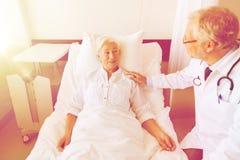 Doctor visiting senior woman at hospital ward Stock Photo