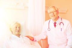 Doctor visiting senior woman at hospital ward Royalty Free Stock Image