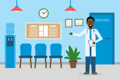 Doctor in waiting room. Handsome smiling african american man in white standing in waiting room. Hospital interior with chairs and health care information Royalty Free Stock Photography
