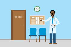 Doctor in waiting room. Handsome smiling african american man in white standing in waiting room. Hospital interior with chairs and health care information Stock Images