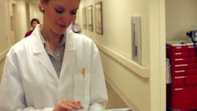 Doctor Walking Along Hospital Corridor Using Digital Tablet