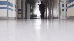 Doctor Walking through the Dark Hallway. In Hospital stock video footage