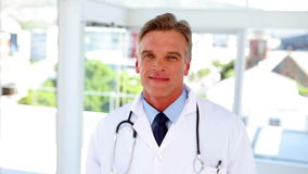 Doctor walking into focus and smiling stock footage