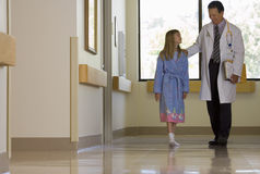 Doctor walking with patient in hospital corridor, girl (10-12) wearing dressing gown, smiling Royalty Free Stock Photo
