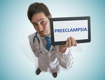 Doctor is warning against preeclampsia disease in pregnant patient. Royalty Free Stock Photography