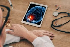 Doctor watching a digital tablet with x-ray of pain in the front of a brain. Migraine headache or trauma concept. Doctor watching a digital tablet with x-ray of royalty free stock photos