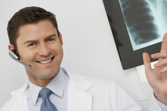Doctor Wearing Bluetooth While Pointing At X-ray Royalty Free Stock Photo