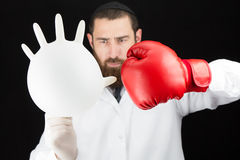 Doctor wearing boxing glove holding inflated glove. Royalty Free Stock Image