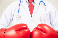 Doctor wearing boxing gloves in white background.  Royalty Free Stock Photos