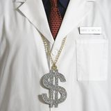 Doctor wearing dollar sign. Stock Photo