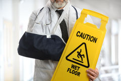 Doctor Wearing Elbow Sling Holding Caution Sign Royalty Free Stock Image