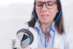 Doctor wearing glasses looking at manometer Royalty Free Stock Images