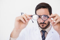 Doctor wearing lab coat looking through eyeglasses Royalty Free Stock Images