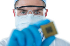 Doctor wearing protective glasses and surgical mask holding electronic chip Royalty Free Stock Photo