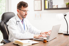 Doctor wearing reading glasses at his office Royalty Free Stock Photography