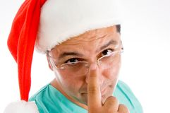 Doctor wearing santa hat adjusting his glasses Royalty Free Stock Photography