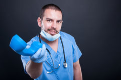 Doctor wearing scrubs handing telephone receiver and smiling. On black background with copy text space Stock Photos