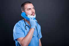 Doctor wearing scrubs holding telephone receiver. On black background with copy text space Royalty Free Stock Images