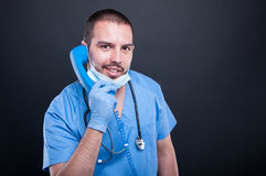 Doctor wearing scrubs holding telephone receiver and smiling. On black background with copy text space Stock Photo