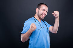 Doctor wearing scrubs with stethoscope making happy success gest Royalty Free Stock Photos