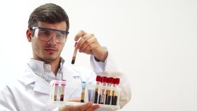 The doctor wearing special laboratory glasses examines test tubes with blood. The doctor is in the laboratory. He wore special transparent glasses. He picks up a stock video footage