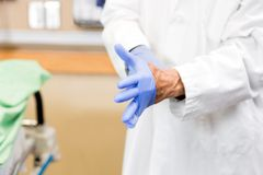 Doctor Wearing Sterilized Gloves In Hospital Stock Photography