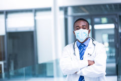 Doctor wearing surgical mask standing with hands crossed Royalty Free Stock Images