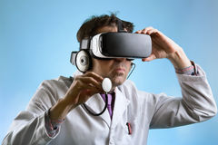 Doctor wearing virtual reality glasses conducting a remote clini Royalty Free Stock Images