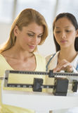 Doctor Weighing Woman On Balance Weight Scale Stock Image
