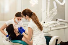 Doctor whit assistant treating teeth of patient, preventing caries. Stomatology concept stock photography