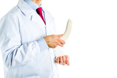 Doctor in white coat bandaging a banana Stock Photos