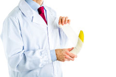 Doctor in white coat bandaging a banana Royalty Free Stock Image