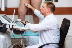 Doctor in a white coat with a clinic with diagnostic equipment. Surgeon man performs an ultrasound using a device on the. Legs of a female patient. Medical royalty free stock photo