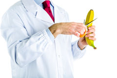Doctor in white coat cutting a banana with scissors Royalty Free Stock Photo
