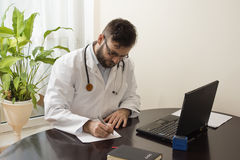A doctor in a white coat in a doctor`s office sits at a table and fills papers Doctor`s office. A doctor at work. A doctor in a white coat in a doctor`s office Stock Photography