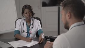 Doctor In White Coat Examining male Patient In Office, blood pressure, african american black nurse in hospital with. Doctor In White Coat Examining Female stock footage