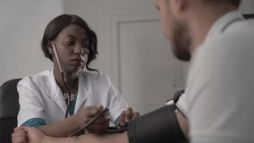 Doctor In White Coat Examining male Patient In Office, blood pressure, african american black nurse in hospital. Doctor In White Coat Examining Female Patient In stock video