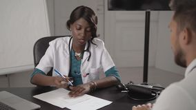 Doctor In White Coat Examining male Patient In Office, blood pressure, african american black nurse in hospital with. Doctor In White Coat Examining Female stock video footage