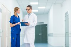 Doctor in white coat and female surgeon discussing diagnosis. In hospital stock photography