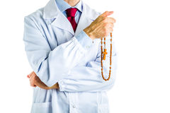 Doctor in white coat holding wooden Rosary beads Stock Images
