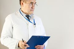 A doctor in a white coat looks into the distance and holds a folder and a pen royalty free stock images