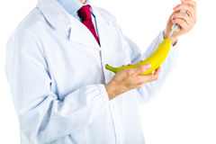 Doctor in white coat making an injection to a banana Stock Photography