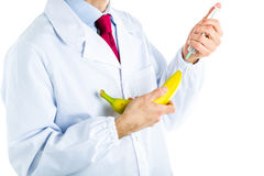 Doctor in white coat making an injection to a banana Royalty Free Stock Photos
