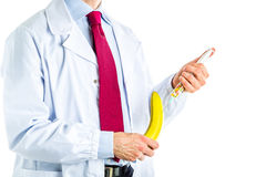 Doctor in white coat making an injection to a banana Royalty Free Stock Image