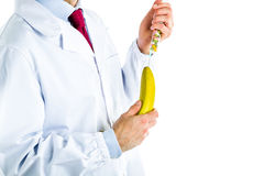 Doctor in white coat making an injection to a banana Royalty Free Stock Photography